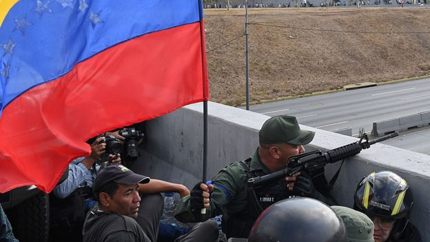 Militares em posição de prontidão e armados em um viaduto de Caracas, ao lado de uma bandeira do país