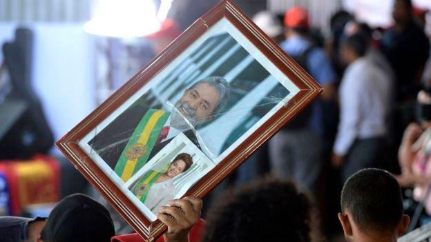 Em protesto, apoiador dos governos petistas levanta quadro com foto de Lula e Dilma com faixas presidenciais