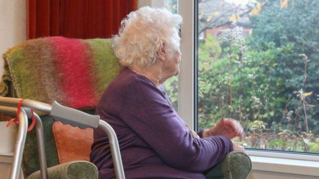 Elderly lady in chair near window