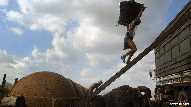 Worker carrying charcoal in Brazil