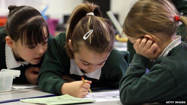 Three primary school girls working at a desk