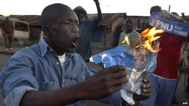 A man burns an election poster in the wake of election results in Kenya in December 2007 which has sparked violence in some areas