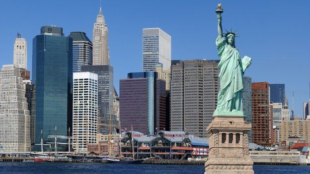 Statue of liberty in front of the Manhattan skyline