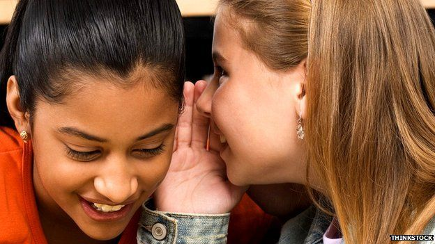One girl whispering in another's ear