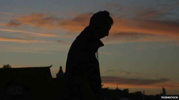 Silhouette of man walking with headphones