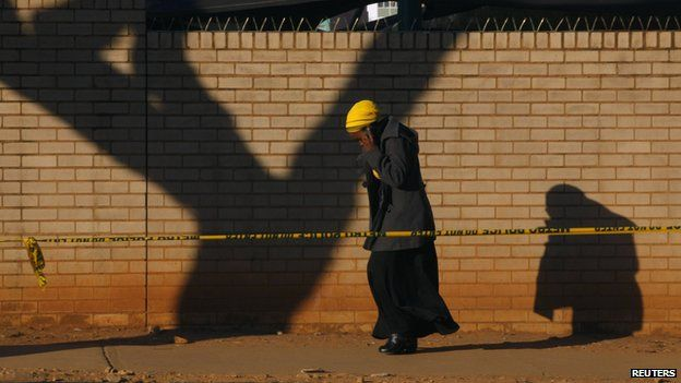 A woman talks on a mobile phone as she walks behind a police cordon outside a Pretoria hospital where former South African President Nelson Mandela is being treated