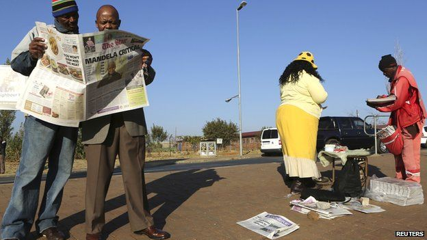Men read a newspaper next to a stall in Soweto on 24 June 2013