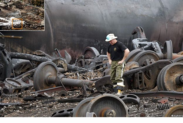 A man inspects the burned remains of the derailed train
