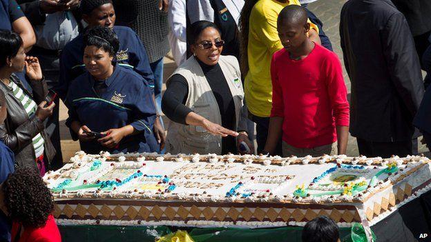 Well-wishers cut up birthday cake outside Mr Mandela's hospital in Pretoria (18 July)