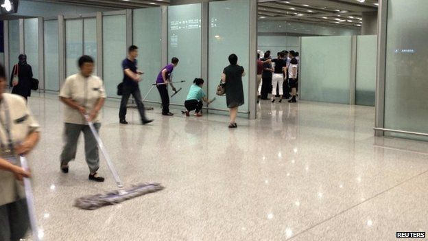 Airport staff clean the floor and glasses at the arrival gate B.