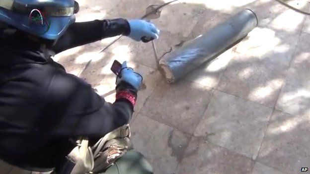 Still from amateur video posted online shows a presumed UN staff member measuring and photographing a canister in the suburb of Muadhamiya in Damascus on 26 August 2013