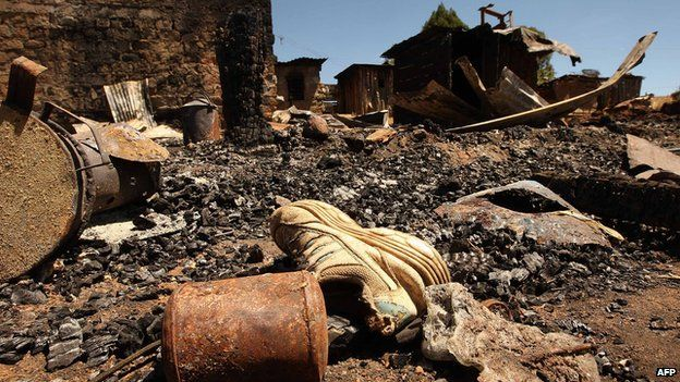 A child's shoe lies on the ground next to a burnt house in Komoyo on 6 January 2008 near Eldoret, Kenya