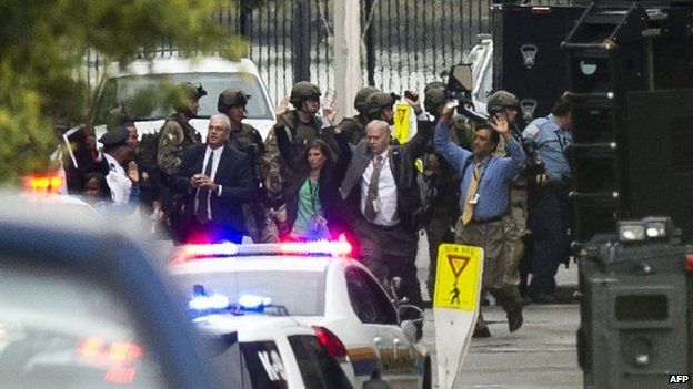 People exit a building with their hands above their heads as police respond to the report of a shooting at the Washington Navy Yard on 16 September 2013