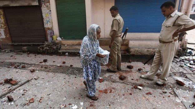 An elderly woman walks on a road scattered with bricks and stones during a communal clash in Muzaffarnagar
