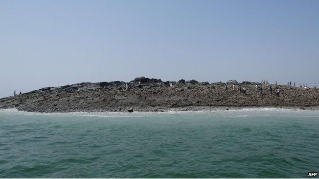 In this photo released by the Pakistani Government, Pakistani men walk on an island that appeared 2 kilometres off the coastline of Gwadar on 25 September, 2013.