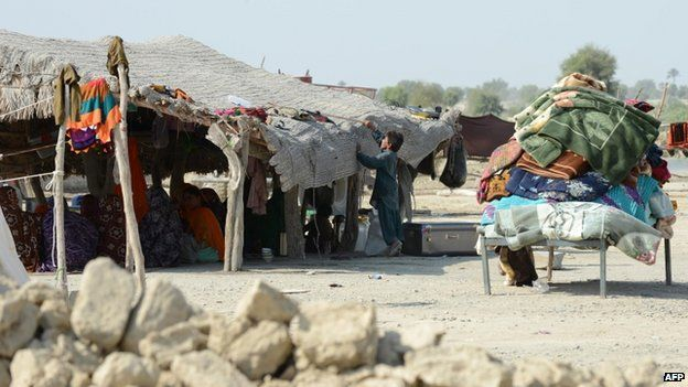 Pakistani earthquake survivor family shelter in a tent near their collapsed mud houses in the Dhall Bedi Peerander area of the earthquake-devastated district of Awaran on 27 September 2013