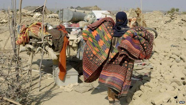 A Pakistani earthquake survivor carries her belongings near her collapsed mud house in the Dhall Bedi Peerander area of the earthquake-devastated district of Awaran on 27 September 2013