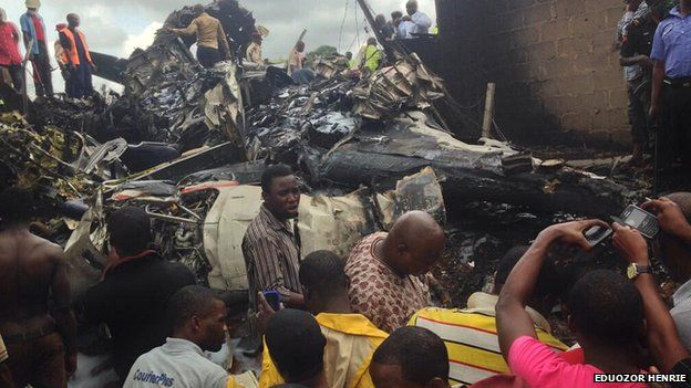 Onlookers gather at the wreckage of a plane in Lagos on 3 October 2013