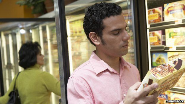 A man looks at a frozen food product
