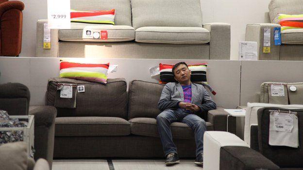 Man sleeps on a chair in Ikea