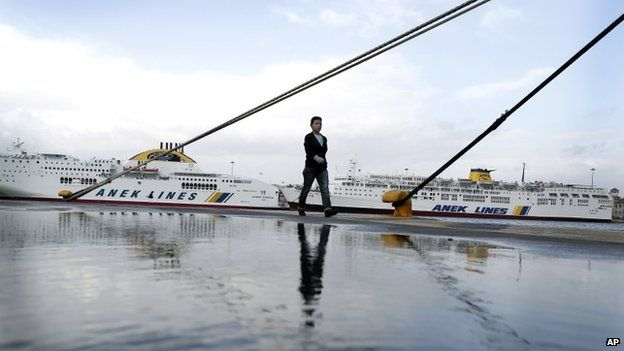 A woman walks in front of docked ships at the port of Piraeus, near Athens, 6 November