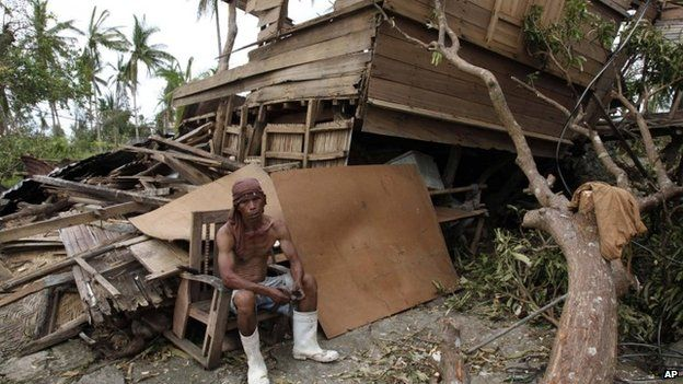 A man salvages wood from his damaged house after the typhoon hit Tabogon town in Cebu province, 11 November 2013