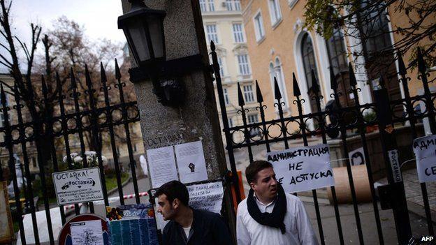 Students stand outside a locked gate of Sofia University, 11 November