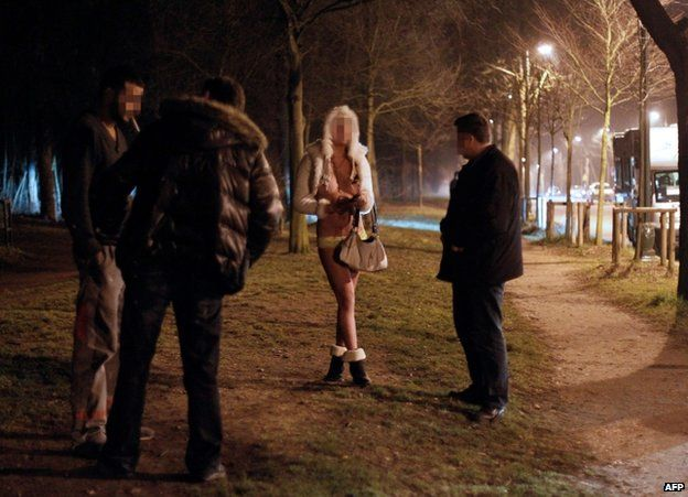 Police officers speak to a prostitute (centre) and a client (left) in the Bois de Boulogne in Paris (file image)