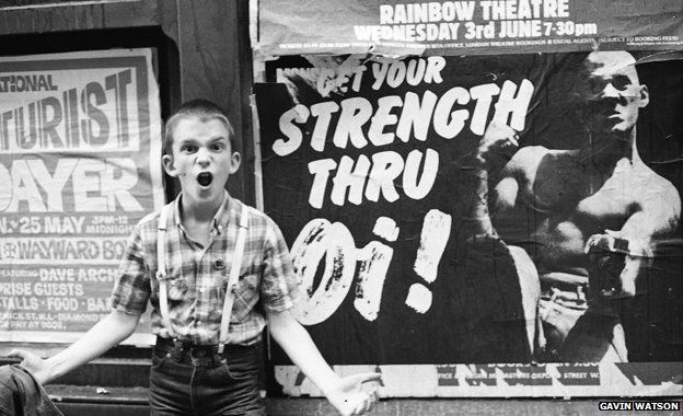 """Photographer Gavin Watson's brother stands in front of a """"Strength thru Oi!"""" poster featuring Nicky Crane"""