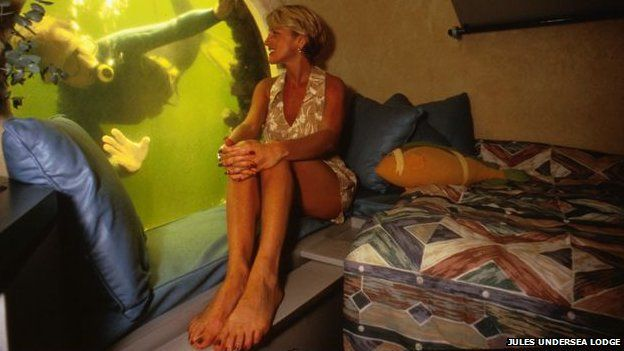 A woman looks out of the window of the Jules Undersea Lodge