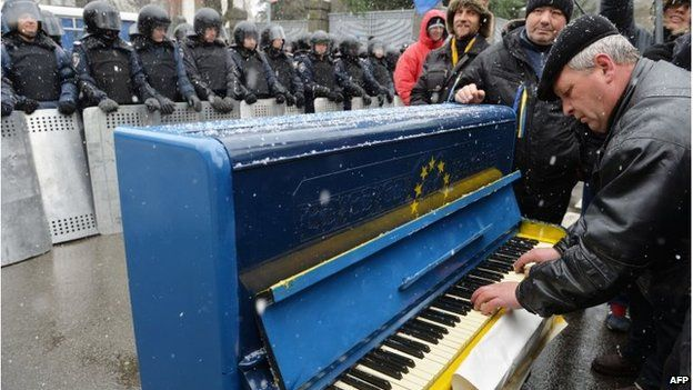 A man plays on a piano decorated with EU flag in front of riot police outside the presidential office