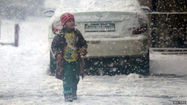 Child walks during snow fall in the Duma neighbourhood of Damascus (13 December 2013)
