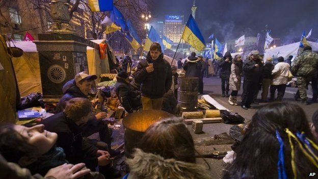 Pro-European Union activists warm themselves by a fire in Kiev