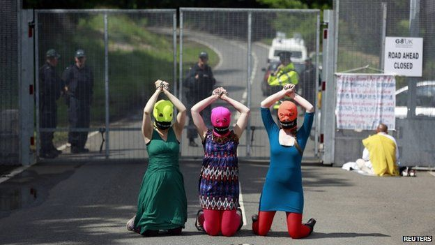 """Demonstrators wear """"Free Pussy Riot"""" balaclavas as they protest at the security fence surrounding the G8 Summit at Lough Erne in Enniskillen, Northern Ireland June 17, 2013"""