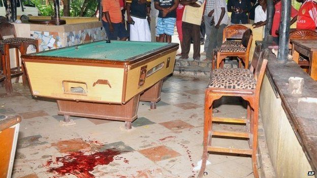 """Members of the public view some blood stains on the floor next to a pool table at the Tanduri Bar and Night Club in Ukunda which is 40km south of Kenya""""s coastal town of Mombasa.,"""