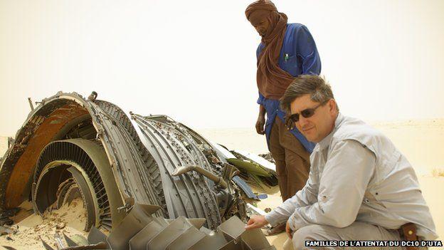 Denoix de Saint Marc kneels next to an engine part lying in the desert