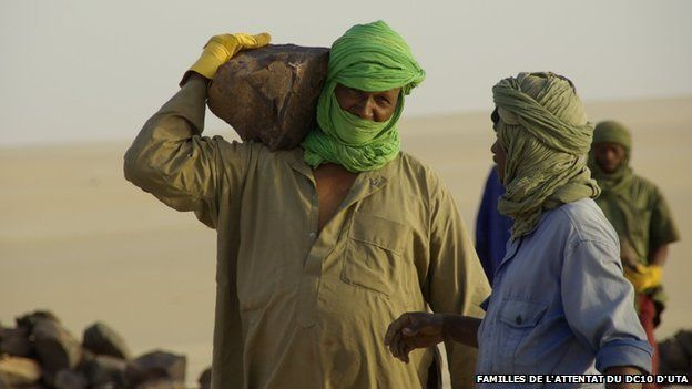 man in colourful headscarf carries a rock on his shoulder