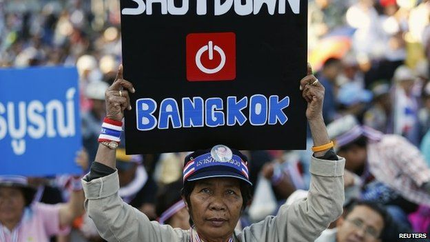 An anti-government protester joins others blocking the road at one of major intersections in central Bangkok on 13 January 2014