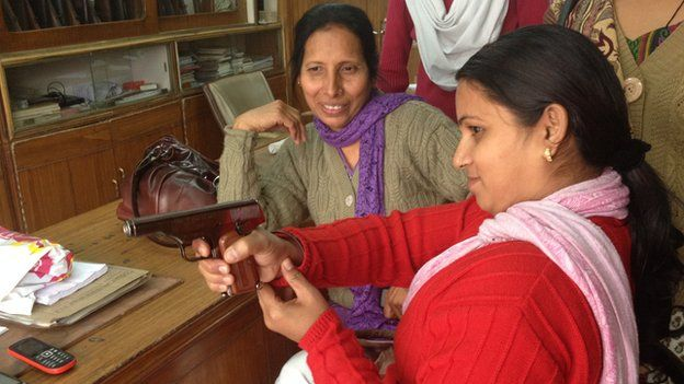 A woman tries out a pistol in a gun shop in Kanpur
