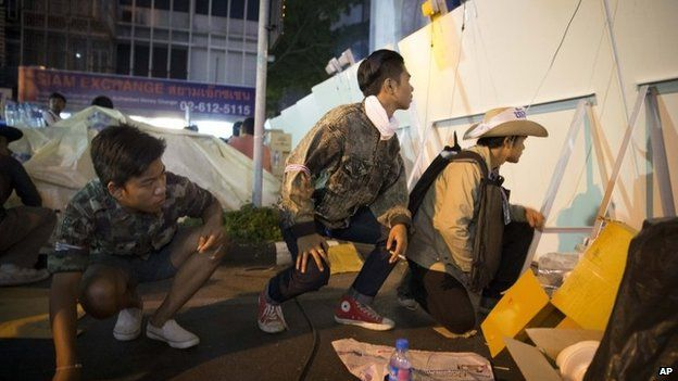 Anti-government protesters duck behind a barricade after shots are heard in the distance near the MBK Centre in Bangkok on 15 January 2014