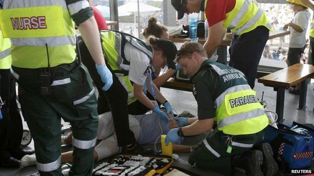 Medics attend to a man who collapsed due to overheating at the Australian Open 2014 tennis tournament in Melbourne, 14 January 2014