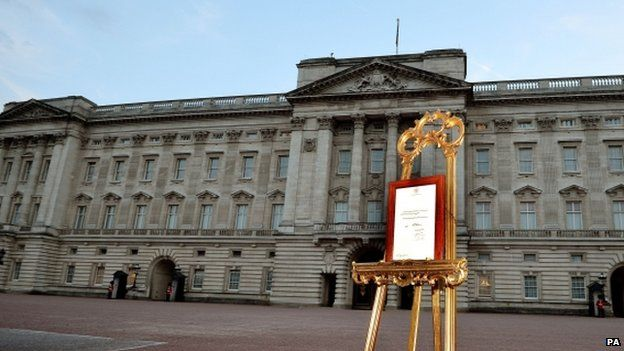 A notice announcing the birth of William and Catherine's baby on display in an ornate easel in the forecourt of Buckingham Palace