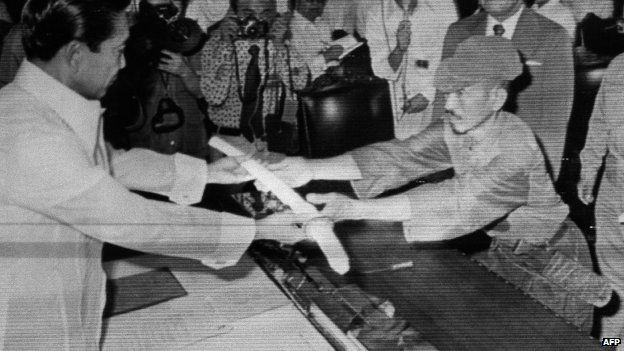 File photo: former Japanese imperial army soldier Hiroo Onoda (right) offering his military sword to former Philippine President Ferdinand Marcos (left) to express his surrender at the Malacanan Palace in Manila, Philippines, 11 March 1974