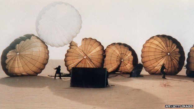 Paratroopers land in the desert with their parachutes