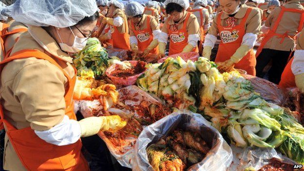 South Korean volunteers make kimchi, a traditional Korean dish of spicy fermented cabbage and radish, in a park outside the metropolitan government building in Seoul, 15 November 2012