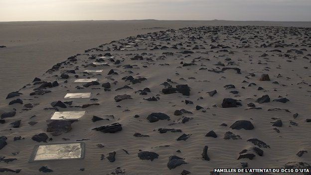 broken mirrors around a black stone circle in the sand