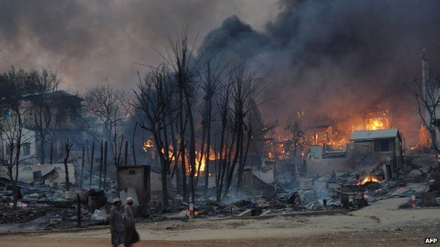 Residents walk past buildings burning in riot-hit Meiktila, central Burma, 21 March 2013