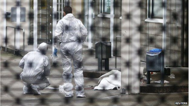 Forensic experts examine the crime scene next to a covered body following the double murder at the courthouse in Frankfurt.