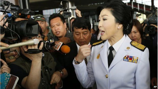 Yingluck Shinawatra speaks to media as she leaves a meeting with election commissioners at the Army Club, Tuesday, Jan. 28