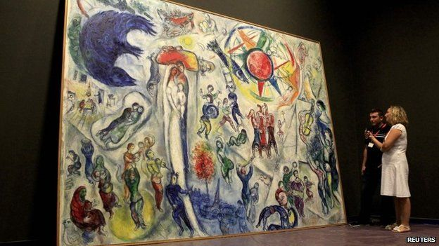 """Museum staff with Chagall's painting """"Life"""" in the Hungarian National Gallery in 2013"""